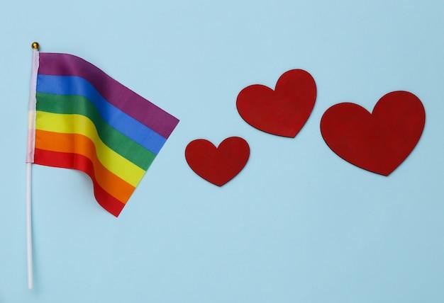 Lgbt 무지개 깃발과 파란색 배경에 하트. 사랑에는 성별이 없습니다. 관용, 자유