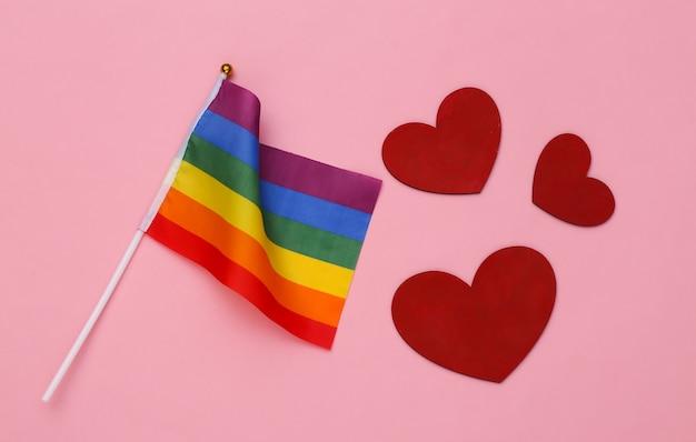 Lgbt 무지개 깃발과 분홍색 배경의 하트. 사랑에는 성별이 없습니다. 관용, 자유