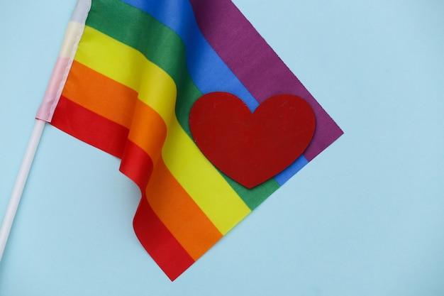 파란색 배경에 lgbt 무지개 깃발과 붉은 마음. 사랑에는 성별이 없습니다. 관용, 자유
