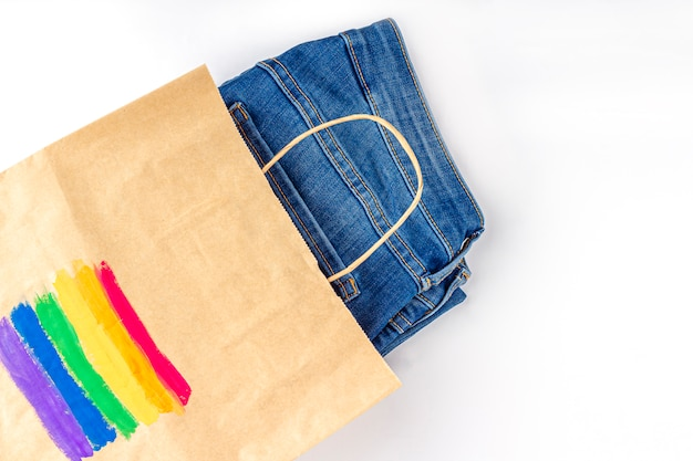 Lgbt rainbow flag painted on a paper gift bag with jeans.