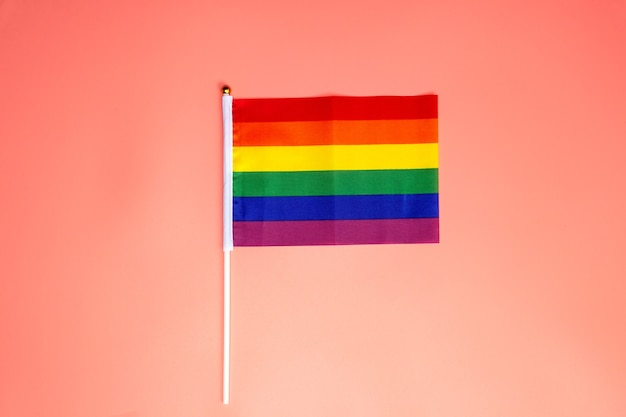 Lgbt rainbow flag, pride flag on pink surface, top view with copy space
