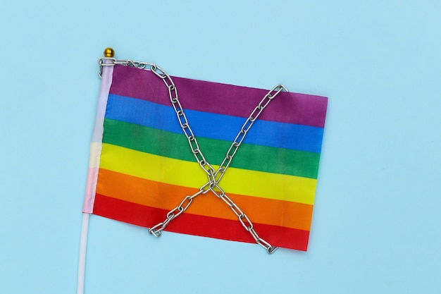 Lgbt rainbow flag wrapped in steel chain. intolerance
