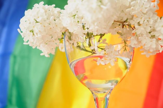 Радужная лгбт-лента и букет белой сирени в стекле. символ ленты гордости. копировать пространство. концепция прав лгбт.