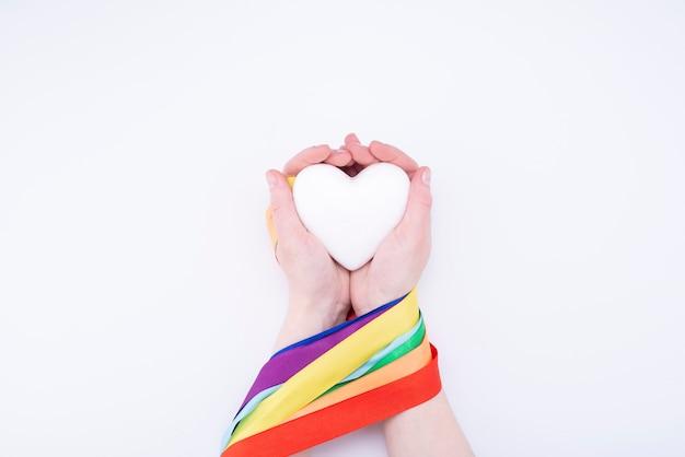 Лента радуги лгбт вокруг руки и сердце на белом фоне. символ гордости ленты