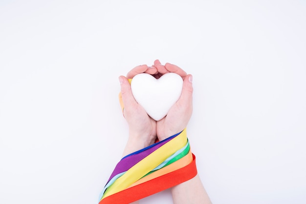 Lgbt rainbow ribbon around hands and heart on a white background. pride ribbon symbol
