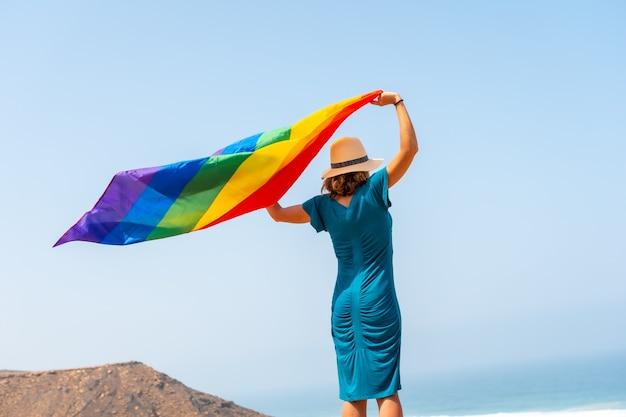 Lgbt 기호, 녹색 드레스와 바다 옆에 무지개 깃발이 달린 흰 모자를 쓴 레즈비언, 동성애의 상징