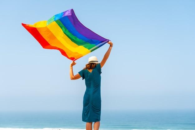 뒤에서 깃발과 푸른 하늘을 배경으로 흔드는 인식할 수 없는 레즈비언인 lgbt 기호