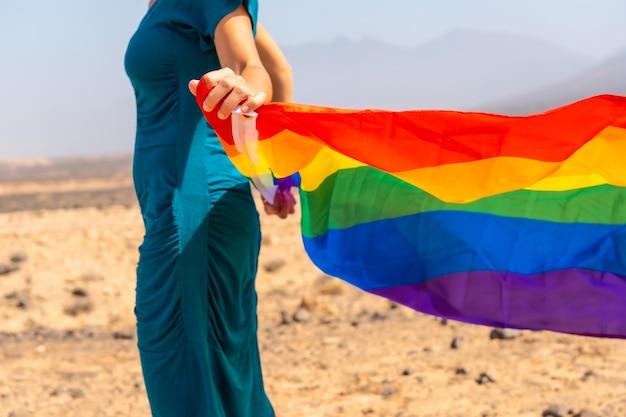 Lgbt 기호, 녹색 드레스와 바다 옆에 무지개 깃발이 달린 흰 모자를 쓴 알아볼 수 없는 레즈비언