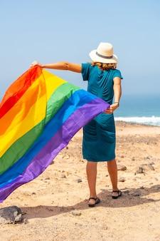 Lgbt 기호, 등을 돌린 인식할 수 없는 레즈비언 사람이 바다에서 깃발을 흔들며 녹색 드레스와 흰색 모자를 쓰고 걸어갑니다.