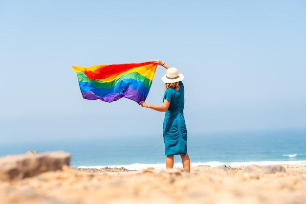 Lgbt 기호, 등을 돌린 인식할 수 없는 레즈비언 사람, 배경에 깃발과 푸른 하늘을 흔들며 동성애의 아이콘