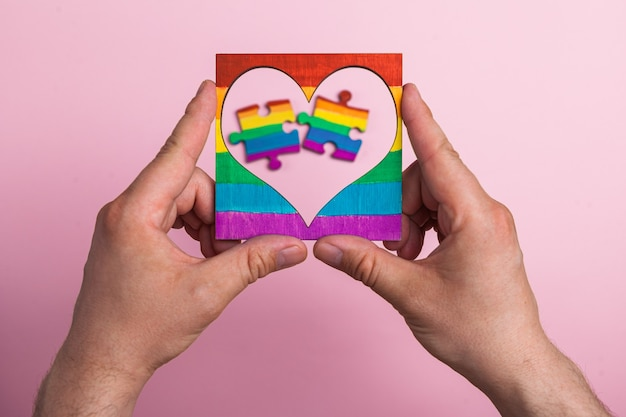 Lgbt symbol frame heart in male hands inside puzzles painted by a rainbow on a medical mask.