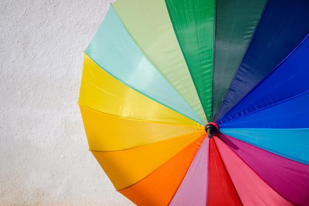 Лгбт-зонтик защищает человека, сияя на солнце многими цветами.