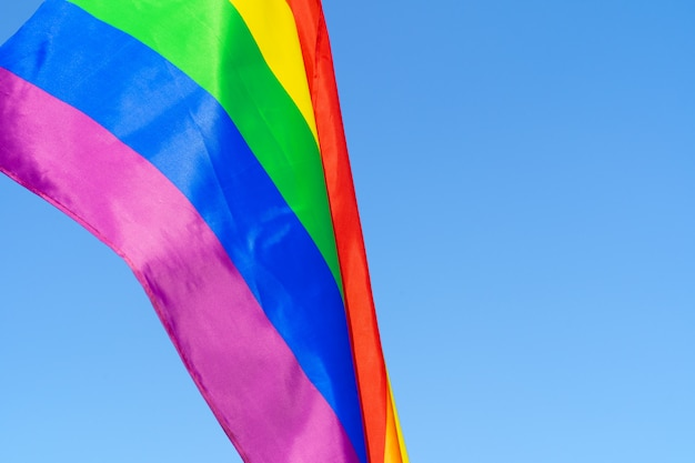 Lgbt waving flag in the sky on flagpole