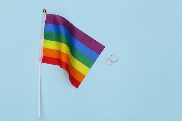 Лгбт-свадьба. радужный флаг лгбт и золотые кольца на синем фоне. терпимость, свобода