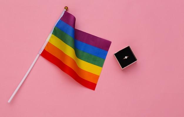 Лгбт-свадьба. радужный флаг лгбт и кольцо в коробке на розовом фоне. терпимость, свобода
