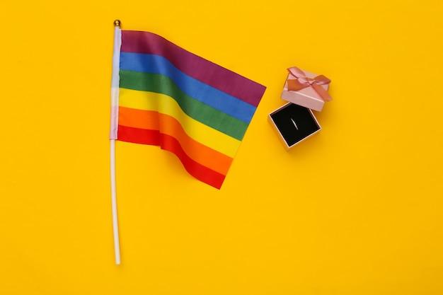 Лгбт-свадьба. радужный флаг лгбт и кольцо в коробке на желтом фоне. терпимость, свобода