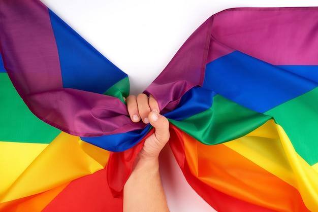 男性の手は、lgbtコミュニティの象徴である虹色の旗を保持しています。