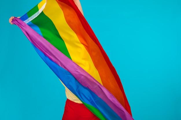 虹色の旗。大きなlgbtフラグを保持し、手を振っている女性