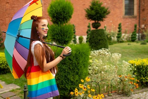 虹の傘でポーズをとって彼女の顔にlgbtフラグ