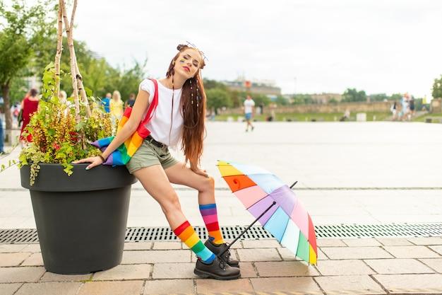 街でポーズをとる彼女の顔にlgbtレインボーのスタイリッシュなバイセクシュアルガール