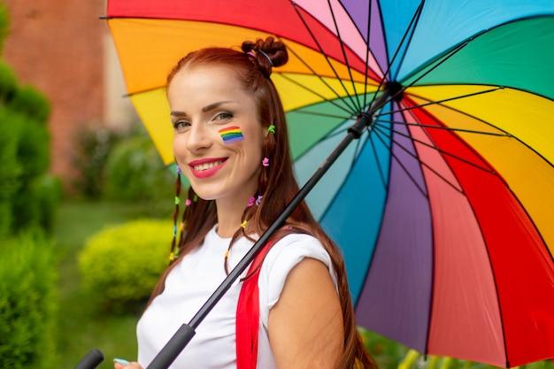 カラフルな服と彼女の屋外でポーズのlgbtフラグで微笑んでいる女の子。