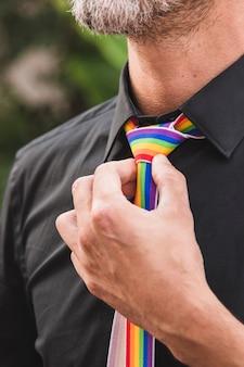 Lgbt色のネクタイの近くに手を持つ男