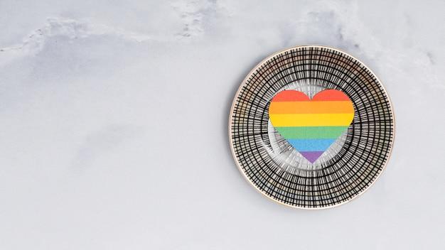 白い背景の上の丸皿に色とりどりのlgbtハート