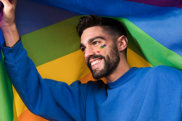 Lgbt虹色の旗を持つ若い笑みを浮かべて男