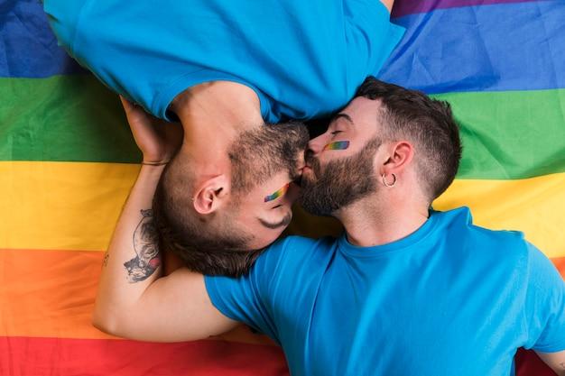 Lgbtの旗に敷設とキスをする男性のカップル