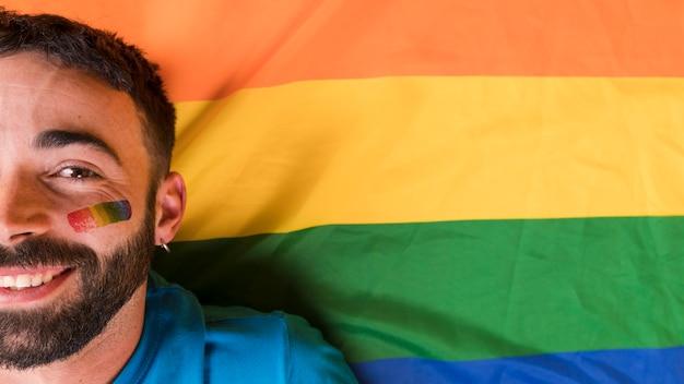 色とりどりの背景上の顔にlgbtの虹のシンボルを持つ男