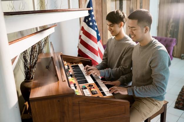 Lgbt男性同性愛者がピアノを弾いています。彼の恋人と喜んで