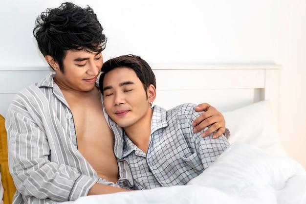 ロマンチックな時間。パジャマ姿のアジアの同性愛者のカップルがベッドで抱擁とキス。コンセプトlgbtゲイ。