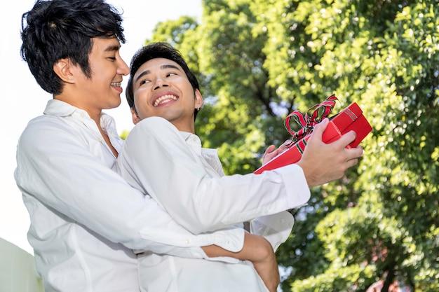 愛の甘い瞬間。アジアの同性愛者のカップルの抱擁と彼氏へのサプライズボックスギフト。コンセプトlgbtゲイ。