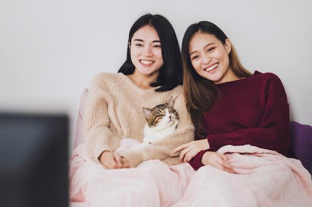 Любовник пар красивых азиатских женщин лесбосский смотря телевидение на кровати с котом совместно в комнате кровати дома с усмехаясь лицом. концепция сексуальности lgbt с счастливым образом жизни совместно.