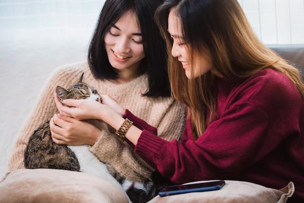 若い美しいアジア女性のレズビアンカップルの恋人は、笑顔で自宅のリビングルームでかわいい猫ペットを再生します。一緒に幸せなライフスタイルとlgbtセクシュアリティの概念。