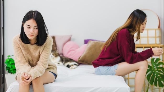 若い美しいアジアの女性レズビアンカップルの恋人は、不機嫌そうな感情で自宅のベッドルームでお互いの紛争の後を強調しました。一緒に動揺と不幸なライフスタイルとlgbtセクシュアリティの概念。