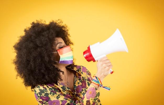Lgbtqの概念。スタジオで隔離の虹色の旗を保持しているアフロ巻き毛のポジティブな白人の女の子