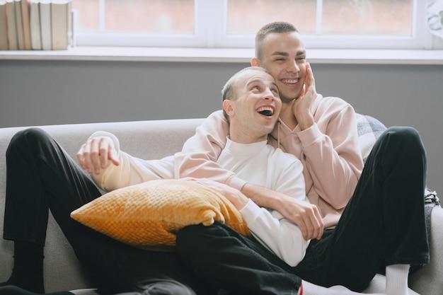 Coppia lgbtq rilassante sul divano. diverso concetto di stile di vita familiare.