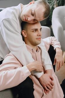 ソファでリラックスしたlgbtqのカップル。異なる家族のライフスタイルの概念。