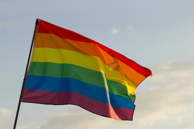 Флаг лгбт или гей-флаг на фоне неба. концепция равенства и гордости.