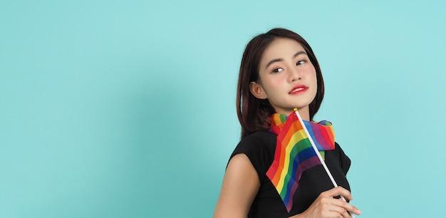 Lgbtqの女の子とプライドフラグ。セクシーなレズビアンの女の子とlgbtの旗が立っています。青緑の背景。