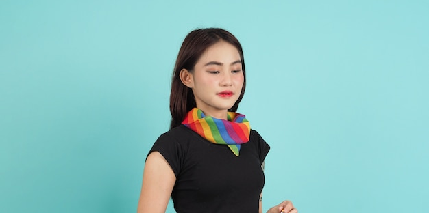 Lgbtq girl and pride flag. sexy lesbian girl and lgbt flag standing. blue green background.