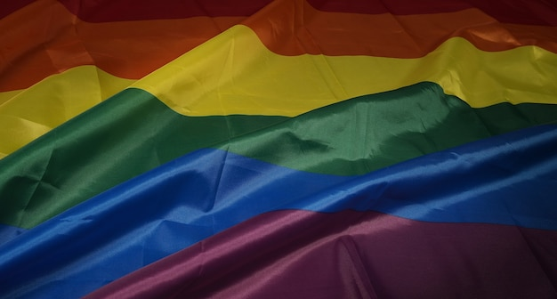 Lgbtqプライドフラグ。レズビアンゲイバイセクシャルトランスジェンダークィア。同性愛者のプライドレインボーフラッグを同性愛者の手に。黒の背景。自由、平和、平等、愛の象徴を表しています。 lgbtqのコンセプト。