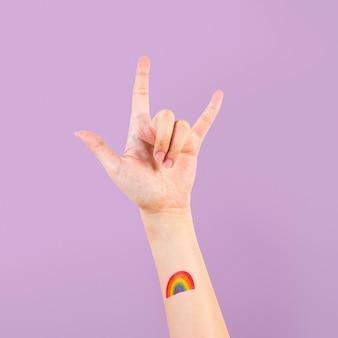 Tatuaggio orgoglio lgbtq+ con rock n' rotolare la mano in aria