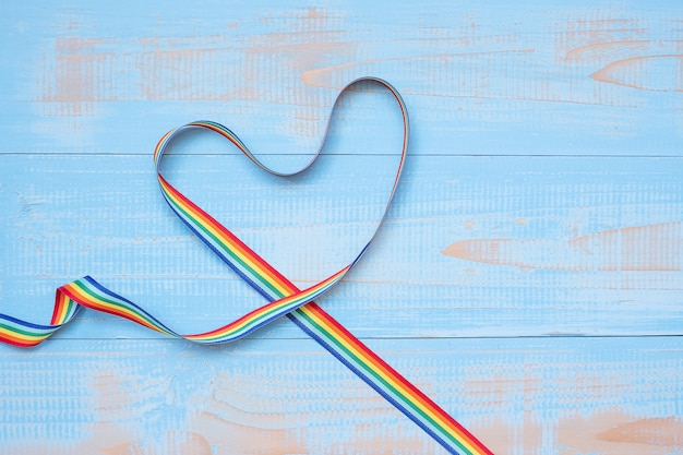 Lgbtq with heart shape rainbow ribbon on blue pastel wooden