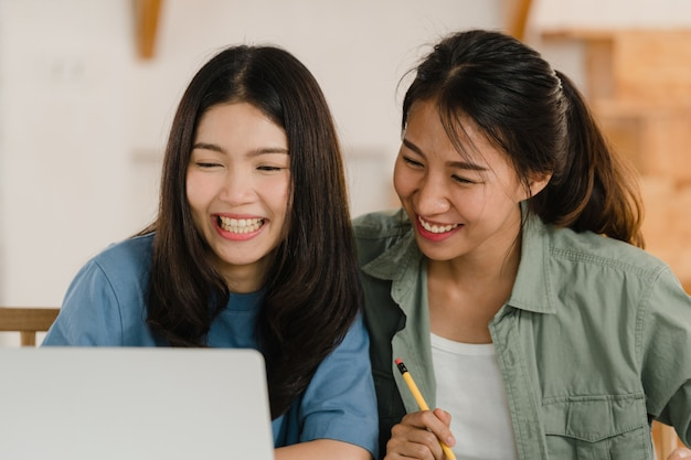 ビジネスアジアのレズビアンlgbtq女性カップルは自宅でアカウントを行います
