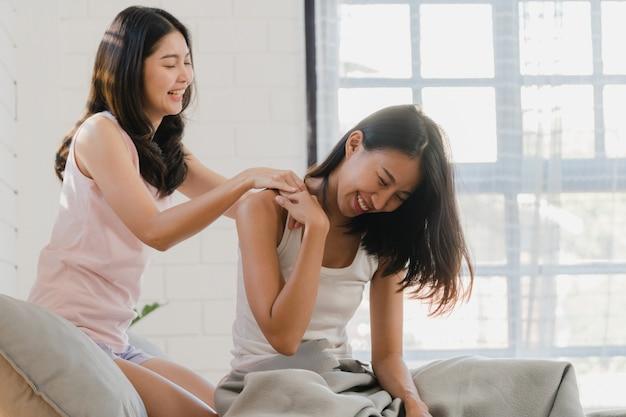 アジアのレズビアンlgbtq女性カップルは自宅でお互いをマッサージします。