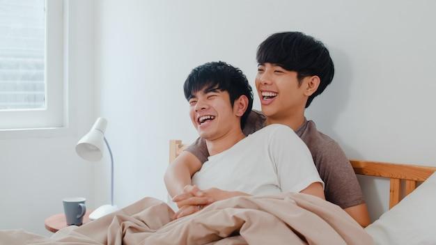 自宅のベッドで話しているハンサムなアジア同性愛者のカップル。若いアジアのlgbtq +男は幸せな休息を一緒にリラックスして、朝モダンな家の寝室で目を覚ました後、ロマンチックな時間を過ごします。