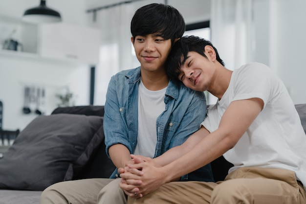 肖像画若いアジアゲイカップルが自宅で幸せな笑顔を感じます。アジアのlgbtq男性は、午前中に自宅の居間のソファーに横たわっている間、カメラを見てこぼれるような笑顔をリラックスさせます。