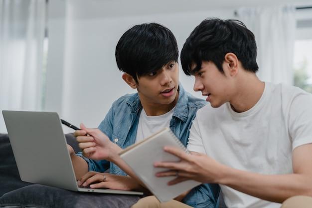 現代の家でラップトップを働く若いアジアゲイカップル。アジアlgbtq +の男性は、コンピューターを使用して、家のリビングルームでソファに横たわっている間インターネットで彼らの財政を一緒に分析して楽しくリラックスします。